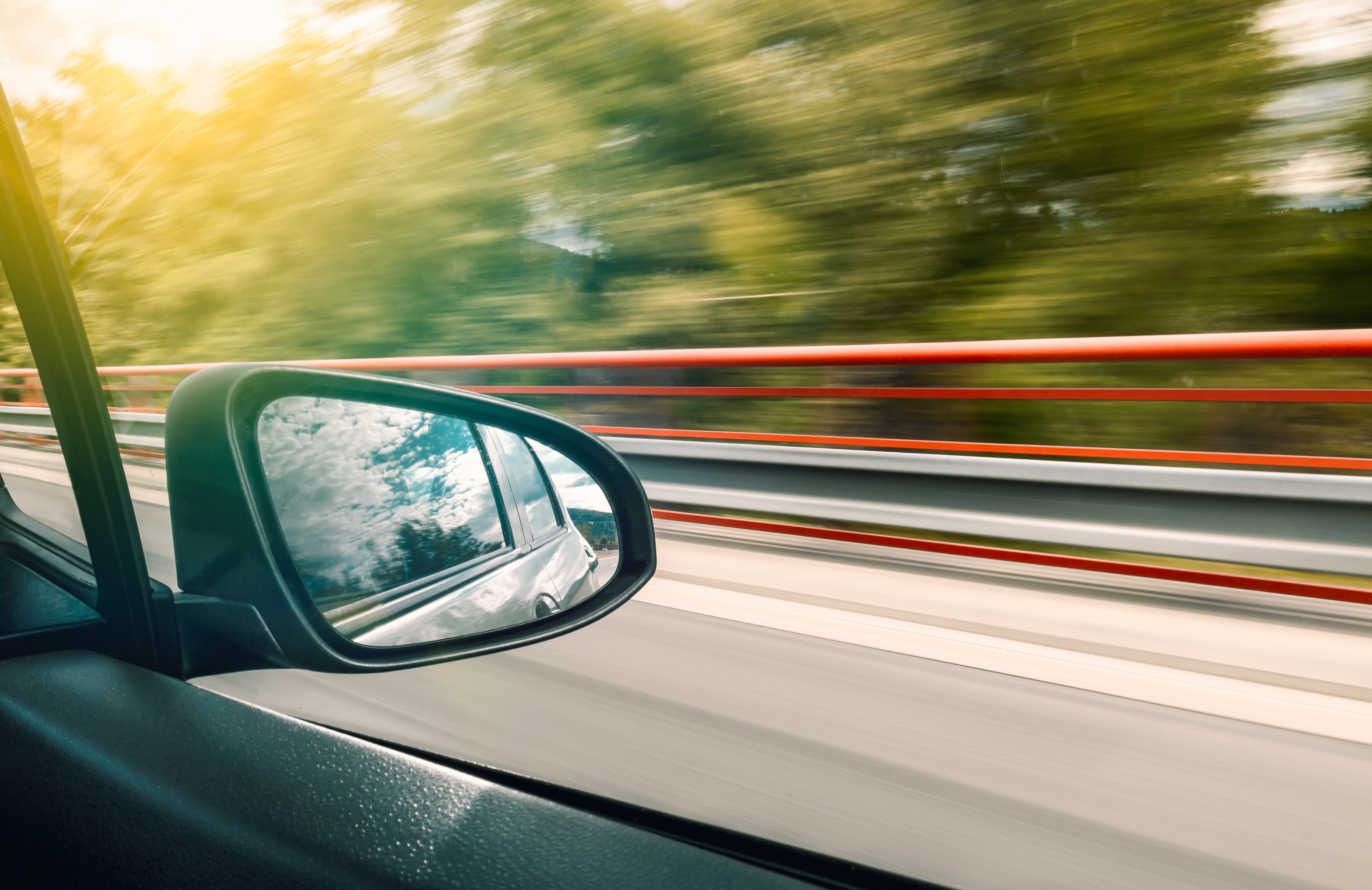 Photo of a car side-view mirror on motorway