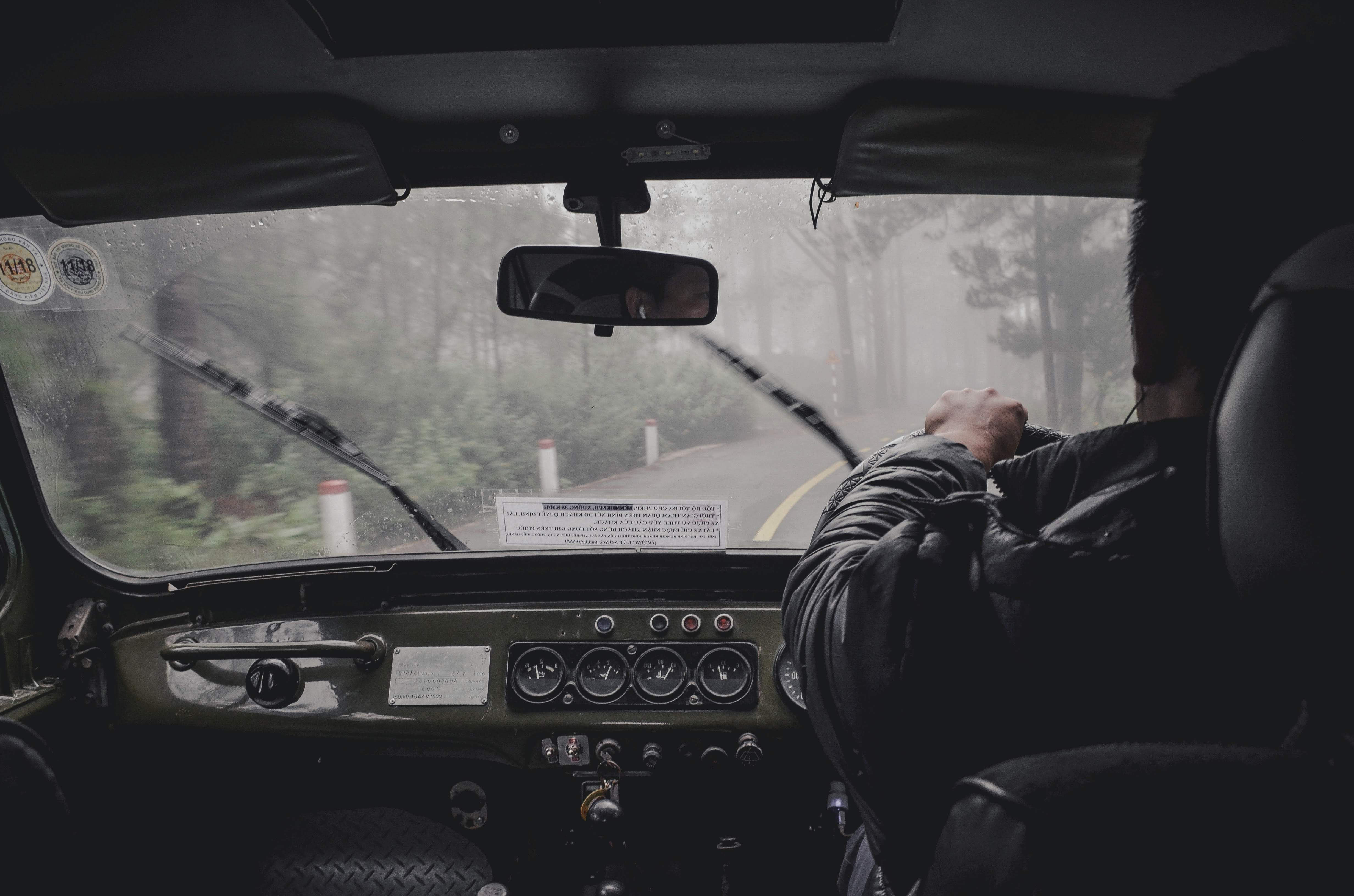 Photo of man driving in rainy woods